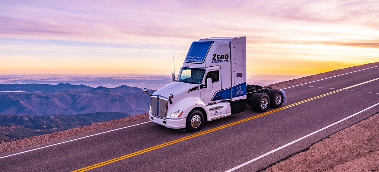 Kenworth zero emission truck driving on the highway during sunrise