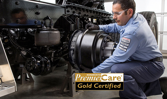 mechanic working on truck with Premier Care logo in the foreground